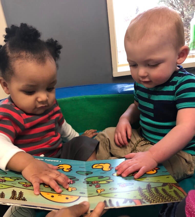 Infants are considering a book at Infants class, at Mt. Elizabeth Academy, Daycare, preschool, Kennesaw Christian school, private school